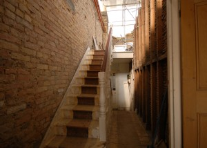 Stairwell where the walls have been hacked back to bare brick and studwork