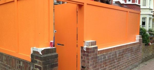 The traditional orange hoarding on the front of the property