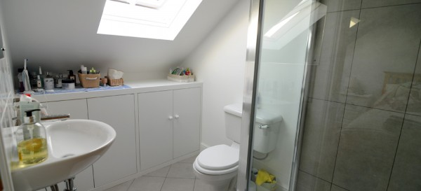 Loft shower room with cupboards