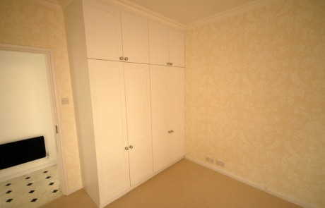 The bespoke wardrobes in the bedroom (note the wallpaper)