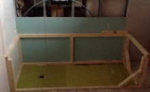 The family bathroom, the tiling and the wooden frame for the bath