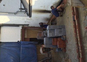 Laying the DPM and first layers of brick on to the concrete slab