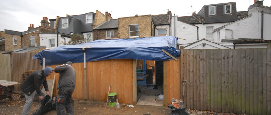 New fencing and rear patio with makeshift roof so we can work in the rain on this rear extension in Earlsfield